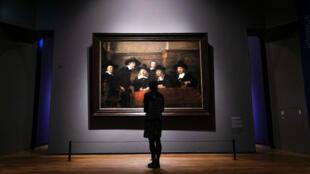 Une femme regarde le tableau de Rembrandt : « Le Syndic de la guilde des drapiers » dans l'exposition « Tout Rembrandt » au Rijksmuseum d'Amsterdam.