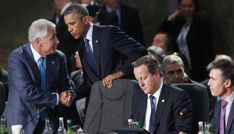 Barack Obama cumprimenta o secretário da Defesa americano, Chuck Hegel, sentado ao lado do premiê britânico David Cameron e do secretário-geral da OTAN (à direita), Anders Fogh Rasmussen.