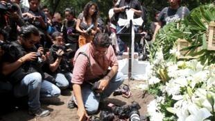 Les photographes ont déposé leurs caméras au sol lors des obsèques du photoreporter Ruben Espinosa assassiné à Mexico vendredi 31 juillet. Son corps et celui de quatre jeunes femmes ont été retrouvés dans un appartement du quartier de Narvarte.