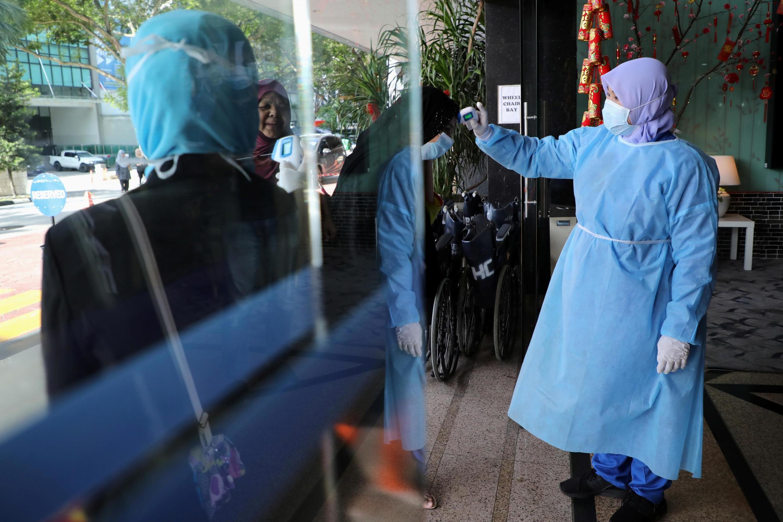 Một y tá đo thân nhiệt người thăm bệnh nhân tại một bệnh viện ở Kuala Lumpur, Malaysia, ngày 03/02/2020.