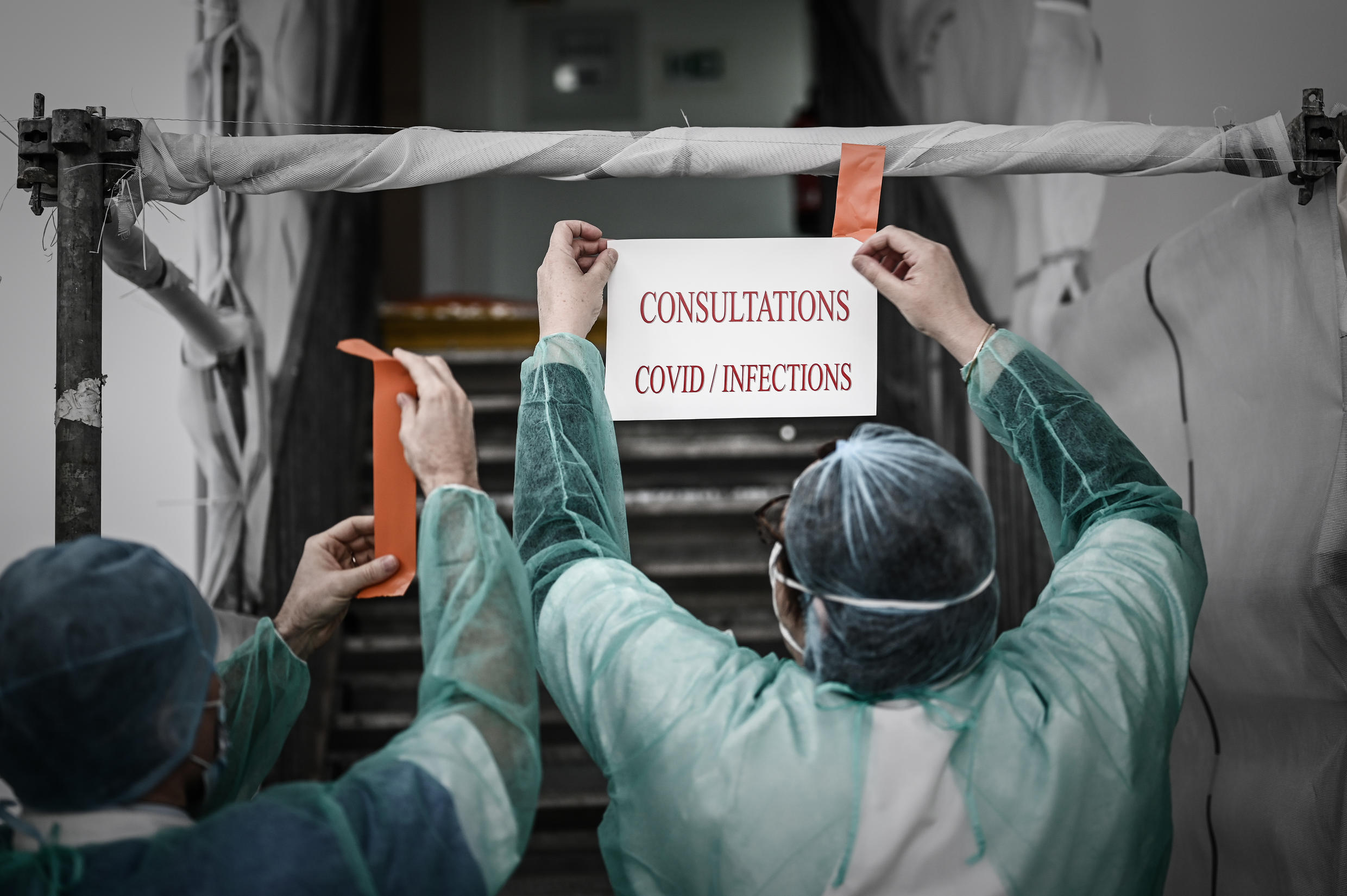 Medical staff stick up a notice at a test centre for COVID-19 in Paris
