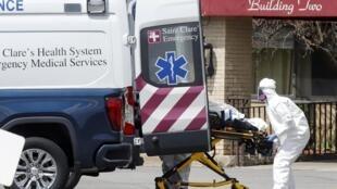 Du personnel paramédical charge un patient dans une ambulance au centre de soins d'Andover, lors de l'épidémie de coronavirus, à Andover, New Jersey, États-Unis, le 16 avril 2020.