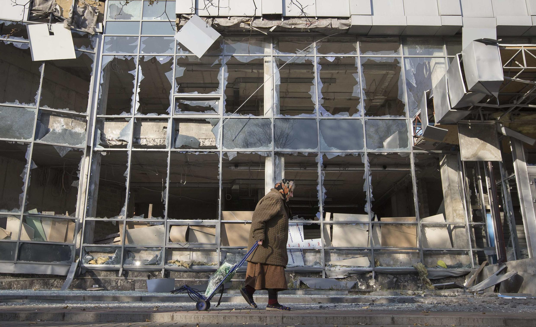 Une vieille femme tire son sac de course devant un bâtiment détruit par les bombardements à Donetsk, dans l'est de l'Ukraine, le 15 octobre 2014.