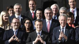Emmanuel Macron forme une tour Eiffel avec ses mains, symbole de la capitale française, lors d'une réunion avec Patrick Baumann (à gauche), président de la commission d'évaluation des Jeux olympiques 2024, le 16 mai 2017 à Paris.