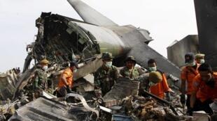 Soldados indonésios e equipes de socorro removem nesta quarta-feira, 1° de julho de 2015, detritos no local do acidente com o avião militar C-130 que caiu ontem em uma área residencial de Medan, na  Indonésia.