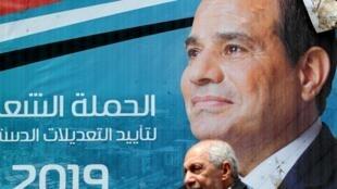 开罗街头,一名男子走过总统塞西的画像