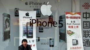 A man yawns in front of a mobile phone shop bearing an advertisement of Apple's iPhone in Beijing April 2, 2013.