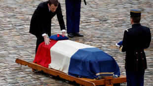 French President Emmanuel Macron touches the flag-drapped coffin of late Gendarmerie officer Colonel Arnaud Beltrame during a national tribute at the Hotel des Invalides in Paris.