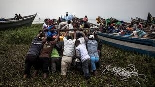 Internally displaced Congolese push a boat out, as its sets off to escape over Lake Albert to Uganda on March 05, 2018 in Tchomia.