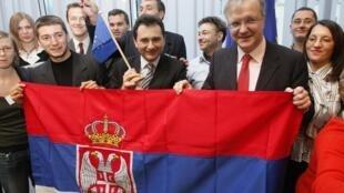 Le vice-Premier ministre serbe, Bozidar Djelic (c) et le commissaire européen à l'Elargissement, Olli Rehn (d) tenant le drapeau de la Serbie,  au milieu d'un groupe de citoyens serbes, à Bruxelles, le 19 décembre 2009.