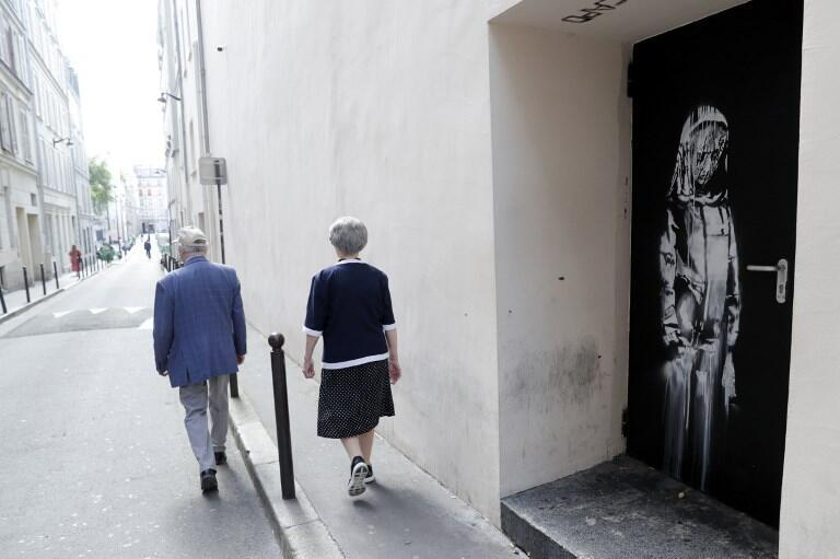 An elderly couple walks past a recent artwork by street artist Banksy in Paris on a side street to the Bataclan concert hall where a terrorist attack killed 90 people on 13 Novembre, 2015.