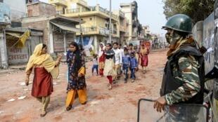 Un groupe de femmes dans une rue du nord-est de la capitale New Delhi à majorité musulmane passent devant un agent militaire, le 26 février 2020 (image d'illustration).