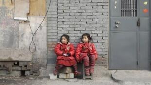 2013年1月12日,北京郊区农民工居住的贫困居民区中,靠墙而坐的两名4岁双胞胎姊妹。