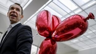 "Artist Jeff Koons poses next to his piece ""Balloon Dog (Red)"" on May 11, 2012 in Basel, Switzerland."