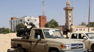 Sur son pick-up équipé d'une mitrailleuse, un combattant des forces pro-gouvernementales tient sa position durant la bataille pour reprendre la ville de Syrte, le 25 juin.