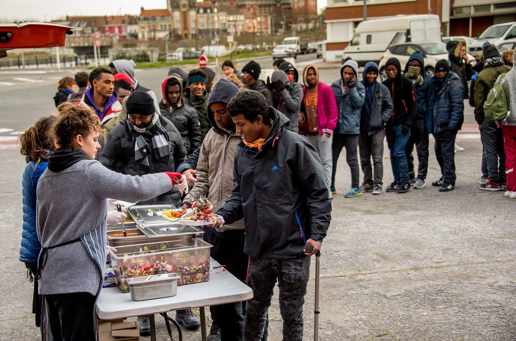 This file photo taken on March 22, 2017 shows volunteers distributing meals to migrants, as the administrative court ordered to not enforce the Calais' decrees prohibiting in certain places the distribution of meals to migrants.