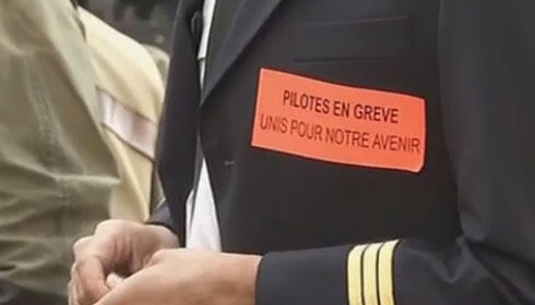 """""""Pilots on strike for our future,"""" reads a sticker on a striker's uniform during a rally in Paris on Tuesday"""