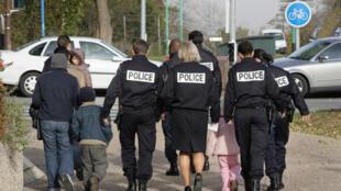 Policiais franceses escoltam família estrangeira para o aeroporto Charles de Gaulle após terem recebido notificação de expulsão por decisão do tribunal.