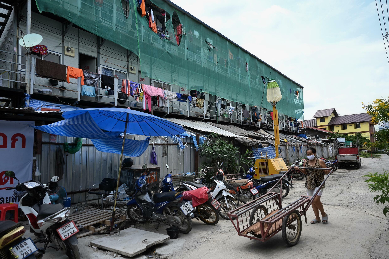 Une femme pousse un chariot à l'extérieur d'un camp où résident des travailleurs de la construction, thaïlandais et birmans, désormais sous confinement en raison des mesures de prévention du coronavirus Covid-19, dans le district de Laksi à Bangkok, le 28 juin 2021.