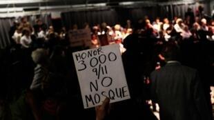 """Un manifestant proteste contre la construction d'une mosquée près de Ground Zero à New York. Sur la pancarte : """"Rendez hommage aux 3000 morts du 11-Septembre"""" ."""