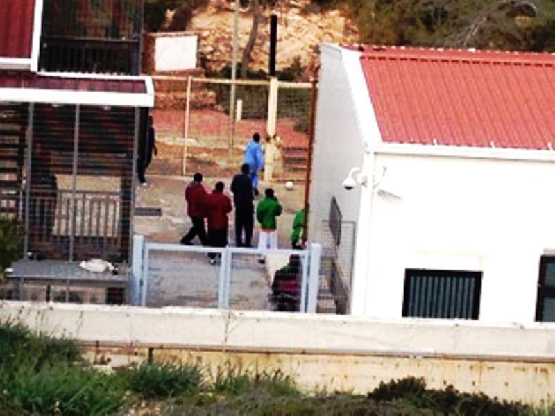 De jeunes Maliens et Sénégalais jouent au foot dans la cour du centre d'accueil des migrants de Lampedusa.