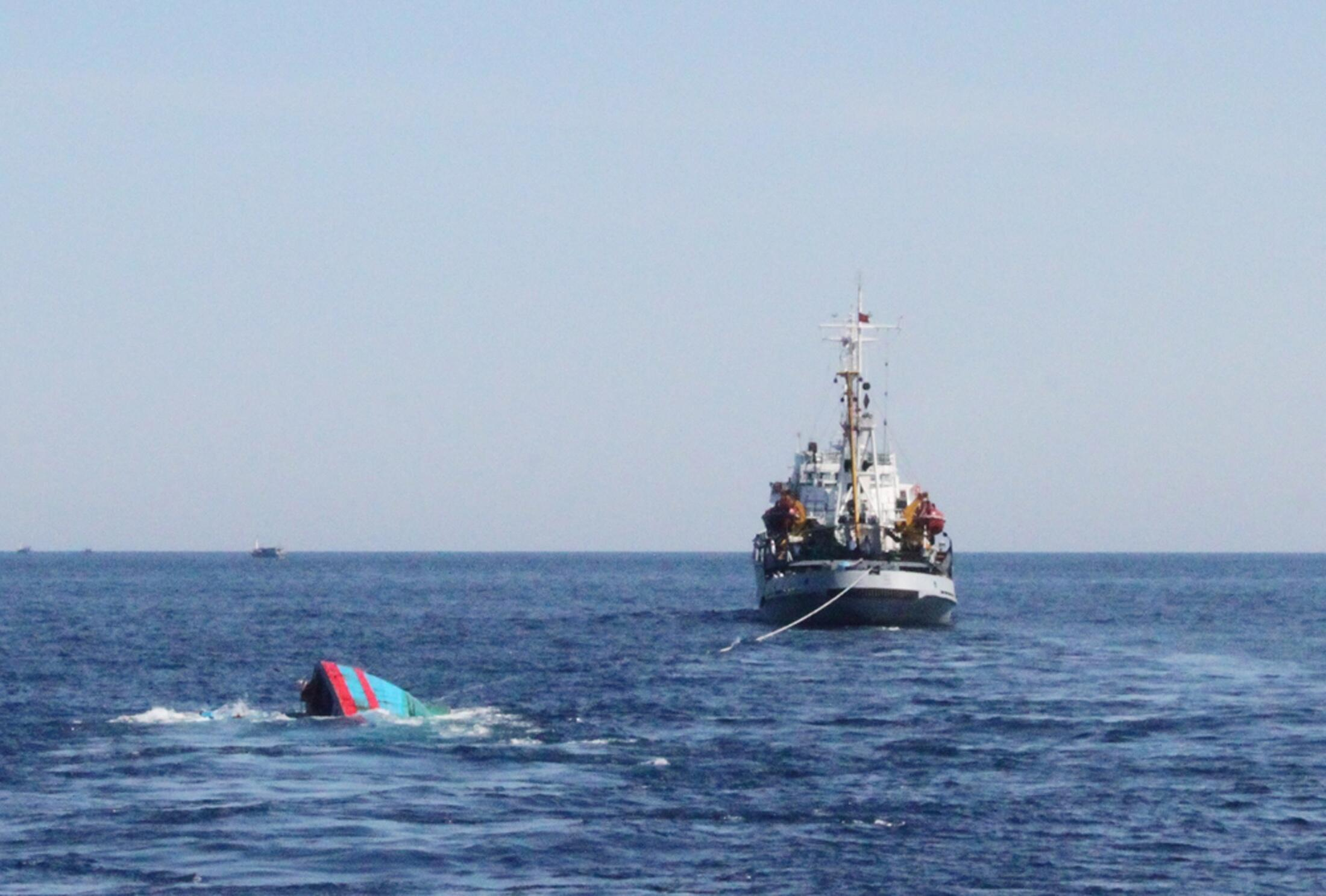 Tàu cá của Việt Nam (T) bị tàu Trung Quốc đâm và chìm, đang được kéo về cảng Lý Sơn, Việt Nam (ảnh chụp 29/05/2014)