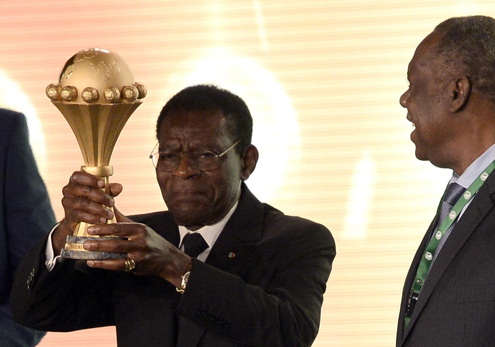 Le chef de l'Etat équato-guinéen, Teodoro Obiang Nguema, soulève le trophée décerné au vainqueur de la Coupe d'Afrique des nations, sous les yeux du président de la Confédération africaine de football, Issa Hayatou, le 3 décembre 2014 à Malabo.