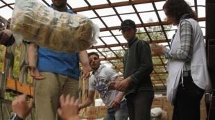 Voluntários ajudam na distribuição de ajuda para os habitantes de Homs, no centro da Síria.