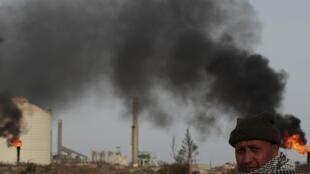 Un rebelle libyen devant un terminal pétrolier repris aux forces de Mouammar Kadhafi à Zueitina (850 km à l'est de Tripoli), le 27 mars 2011.
