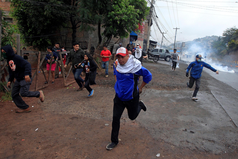 Des manifestants à Tegucigalpa, échappant aux gaz lacrymogènes, le 18 décembre 2017.