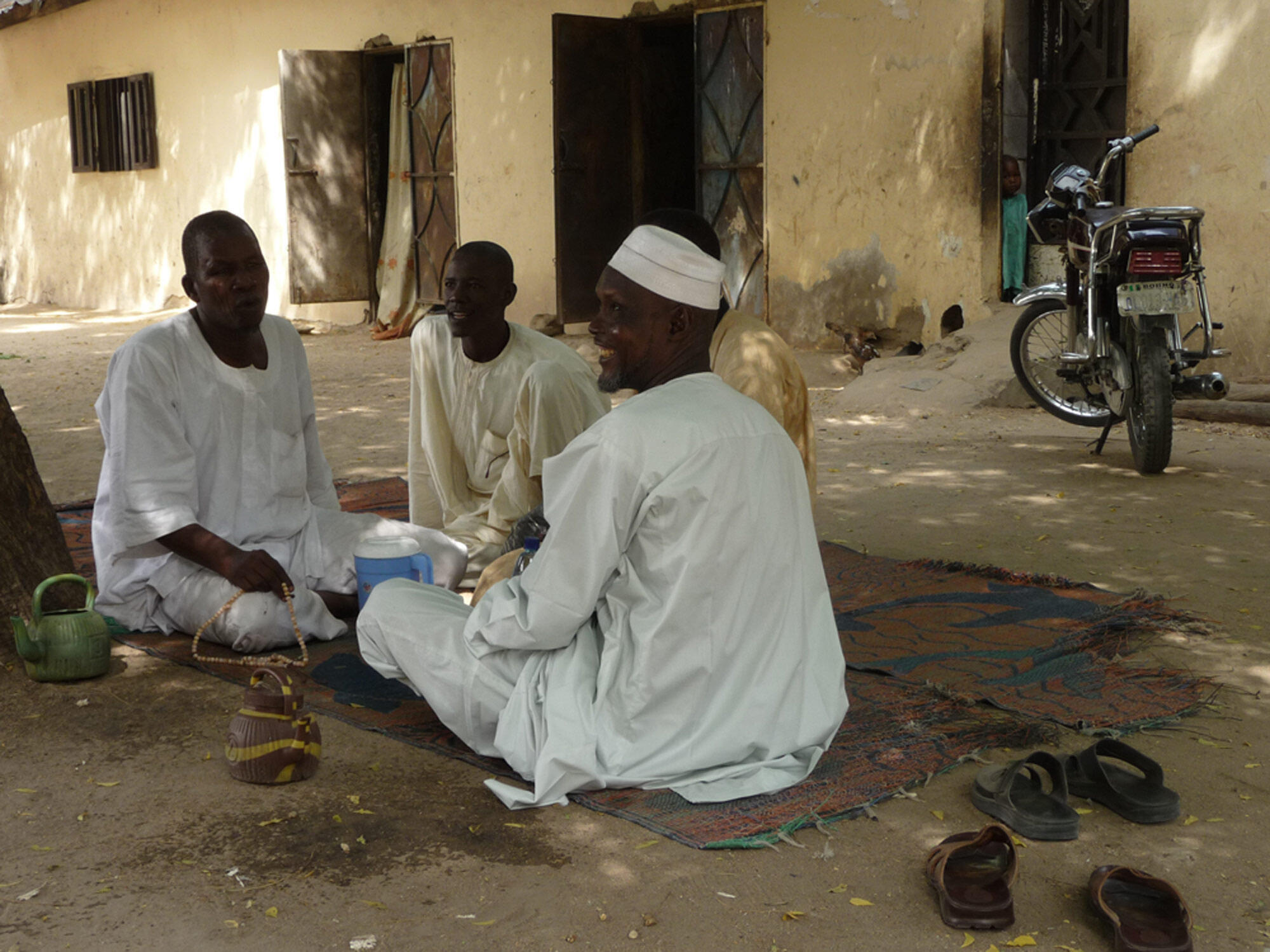Des hommes assis sur des nattes dans un quartier populaire de Maiduguri.