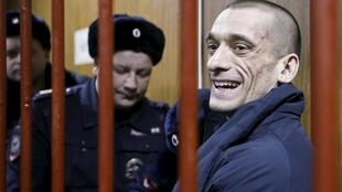 Artist Pyotr Pavlensky reacts inside a defendants' cage during a court hearing in Moscow, Russia, February 26, 2016.