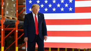 El presidente de Estados Unidos, Donald Trump, pasa junto a una bandera nacional  durante una visita a las instalaciones de Puritan Medical Products en Guilford, Maine, el 5 de junio de 2020.
