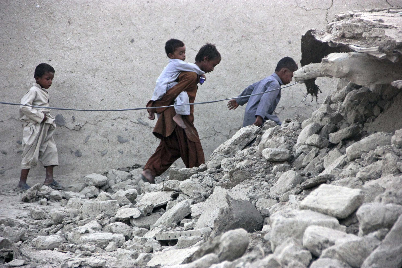 Sobreviventes deixam escombros depois do terremoto que atingiu o Paquistão na terça-feira