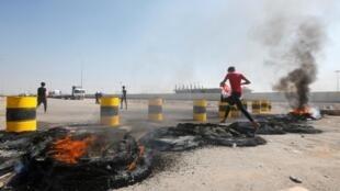"""معترضین عراقی با آتش زدن لاستیک ماشینها، جادههای منتهی به بندر """"ام قصر"""" در جنوب بصره را مسدود میکنند. شنبه ١١ آبان/ ٢ نوامبر ٢٠۱٩"""