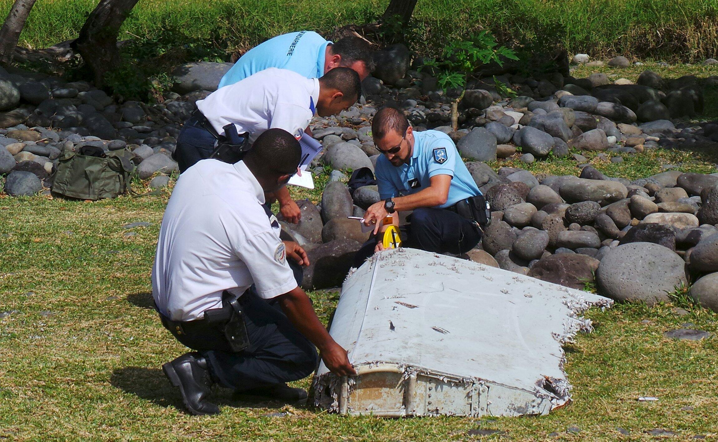 Французские жандармы и полицейские исследуют обломок самолета, найденный на пляже острова Реюньон, 29 июля 2015.