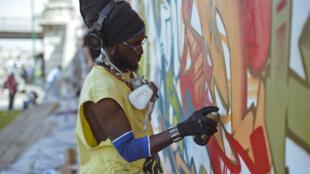 Le graffeur sénégalais Docta à l'œuvre à Paris.