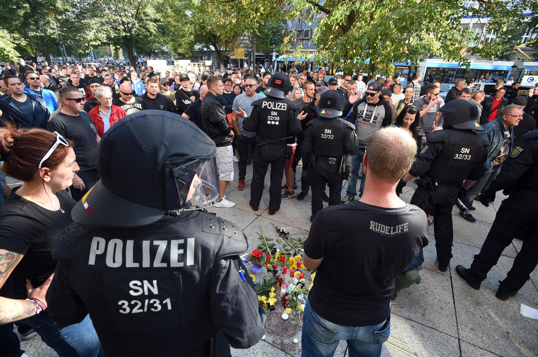"""Forças de segurança e manifestantes da extrema-direita, ao lado de um memorial improvisado em Chemnitz, Alemanha, após a morte de um alemão de 35 anos, em """"uma briga com pessoas de diferentes nacionalidades"""", segundo a polícia. 26/08/18"""