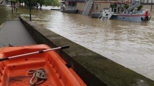 Une barque posée en bordure de quai pour atteindre les péniches isolées dans la Seine.
