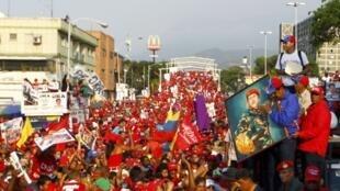 Partidários do candidato Nicolás Maduro (à dir. com a foto de Chávez nas mãos) durante comício na cidade de Vargas, na terça-feira, 9 de abril.