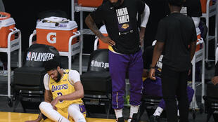 Los Angeles forward Anthony Davis falls at the Lakers bench in the first quarter of the NBA champions' season-ending loss to the Phoenix Suns in game six of their Western Conference first-round playoff series