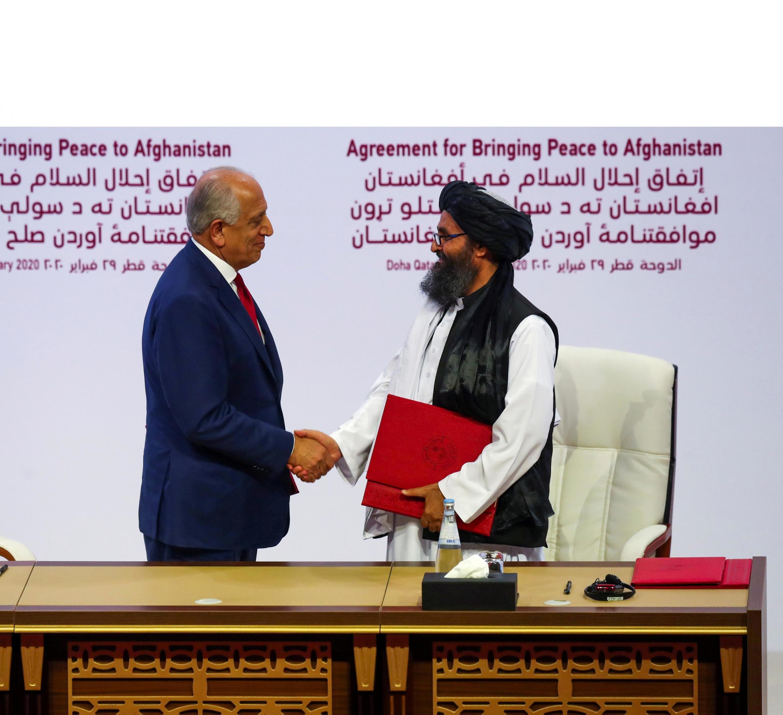 ملا عبدالغنی برادر، رئیس هیأت طالبان و زلمای خلیلزاد، نماینده آمریکا در مذاکرات افغانستان، پس از امضاء توافقنامه صلح میان آمریکا و طالبان در قطر. شنبه ١٠ اسفند/ ٢٩ فوریه ٢٠٢٠