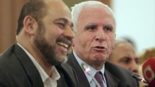 Azzam al-Ahmed (D) du Fatah et Moussa Abou Marzouk du Hamas, après une conférence de presse au Caire le 27 avril 2011.