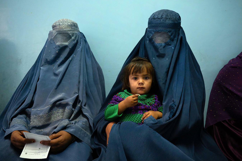 Mujeres sentadas esperan con un niño en la clínica de Tangi Saidan en el centro de Afganistán, el 6 de octubre de 2021