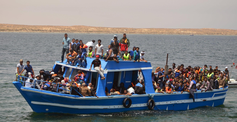 Imigrantes ilegais em um barco no Mediterrâneo após serem resgatados pela marinha da Tunísia.