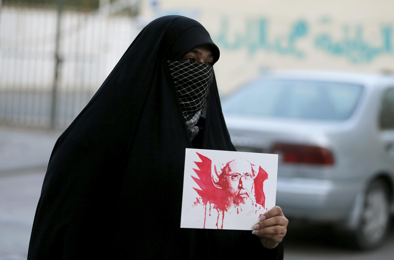 Manifestante exibe retrato do xeque Al-Nimr banhado de sangue durante protesto no Bahrein, em 2 de janeiro de 2016.