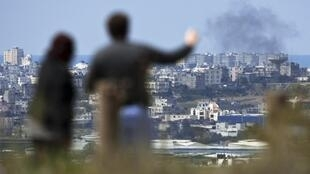 Ces gens observent de loin la bande de Gaza, où une fumée s'échappe suites aux échanges de tirs entre Israël et le Hamas, le 25 mars 2011.