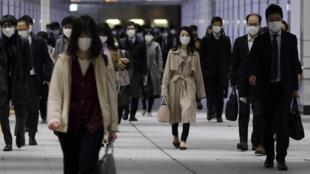 Unos viajeros japoneses se dirigen a sus puestos de trabajo el 9 de abril de 2020 desde la estación de tren de Shinjuku, en Tokio