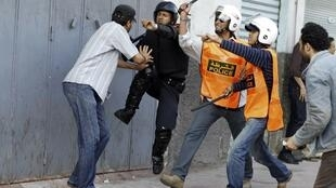 Manifestant pris à partie par des policiers à Casablanca le 29 mai 2011.