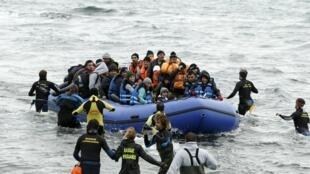Voluntarios se acercan a una embarcación repleta de refugiados en la isla griega de Lesbos, el 29 de enero de 2016.